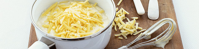 A bowl of cheese sauce toppe with grated cheese