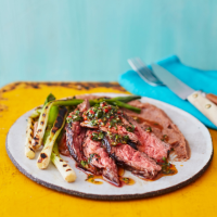 Steak with blackened salad onions, refried beans and chimichurri