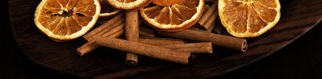 Cinnamon sticks with slices of orange on a plate