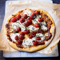 Pizza with mozzarella, rosemary, roasted tomatoes & black olives