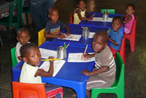 A group of children drawing at tables in a crèche