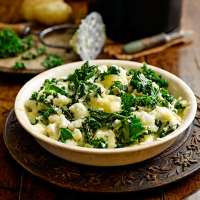 Cauliflower and potato mash with kale and melting brie